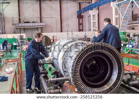 Tyumen, Russia - November 14, 2007: JSC Tyumenskie Motorostroiteli (Plant on production and repair of aviation engines). Workers assemble turbine of aviation engine - stock photo