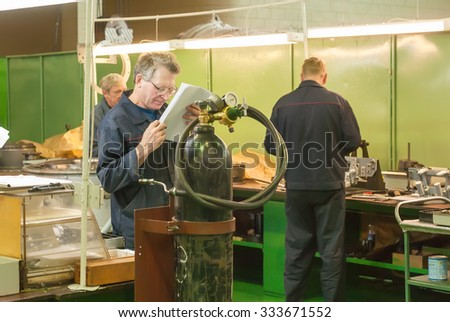Tyumen, Russia - November 14, 2007: JSC Tyumenskie Motorostroiteli. Plant on production and repair of aviation engines. Elderly mechanic wearing spectacles reads drawing in shop - stock photo