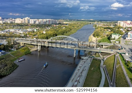 Tyumen, Russia - September 3, 2015: Aerial view of Tura river and bridge on Chelyuskinskaya street. Nearby there is construction of new one.