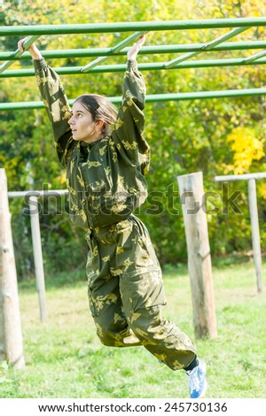 Tyumen, Russia - September 22, 2012: Avanpost training center on preparation of school students for army. Miles of Fire festival of live history. Teenage girl on climbing frame in militarized relay - stock photo