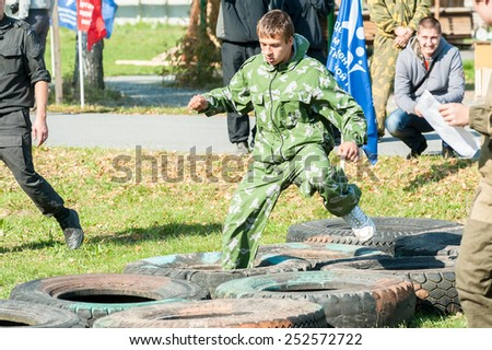 Tyumen, Russia - September 22, 2012: Avanpost training center on preparation of school students for army. Miles of Fire festival of live history. Cadet passes sports stage of relay - stock photo