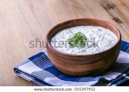 Tzatziki. Greek salad tzatziki  of cucumber, yogurt or cream, olive oil, garlic, dill and spices. Herb decoration of dill. - stock photo