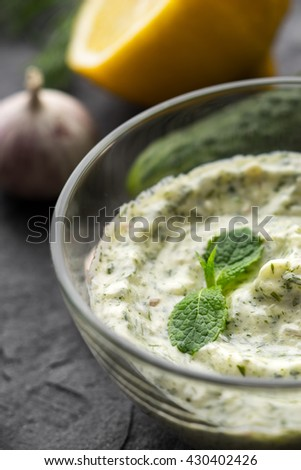Tzatziki in the glass bowl on the black stone table vertical