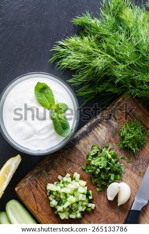 Tzatziki sauce preparation - yogurt in glass bowl, cut cucumber, mint, dill on wood board, knife, dark stone background, top view, closeup - stock photo