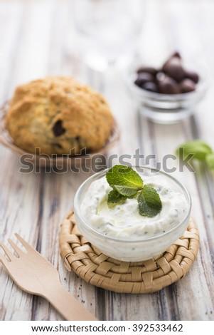 Tzatziki with olive bread on white table - stock photo