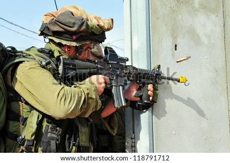 TZEELIM - MARCH 31: Israeli soldier shoots during Urban Warfare Exercise on March 31 2011 in Tzeelim, Israel. The complexity of the terrain and civilians makes it very difficult to identify the enemy