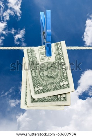 u.s. dollar on rope with clothespin over blue sky - stock photo