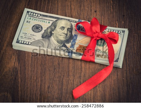 U.S. dollars banknotes with a red ribbon as a gift of money - stock photo