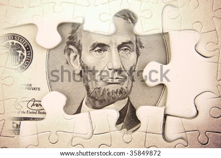 U.S. five dollars and puzzle pieces - stock photo