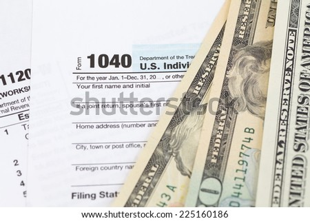 U.S. income tax form and dollar bill - stock photo