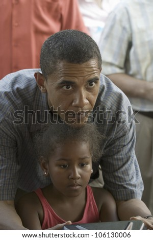 U.S. Senator Barak Obama playing game with his daughter while campaigning for President at Iowa State Fair in Des Moines Iowa, August 16, 2007 - stock photo