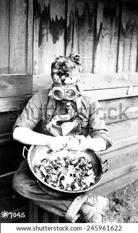 U.S. soldier putting his respirator to good use while peeling onions. 40th Division, Camp Kearny, San Diego, California. WWI. March 1918.