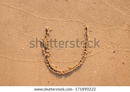 U text written in the sandy on the beach - stock photo
