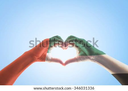 UAE national labour day celebration symbolic concept: United Arab Emirate color flag pattern on people hands heart shape bright blue sky background showing unity, labor, friendship, harmony nation   - stock photo
