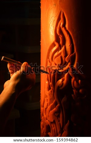 Ubon Ratchathani, Thailand - July 4, 2012: A craftsman was carving a traditional Thai style pattern on a candle using a carving tool.
