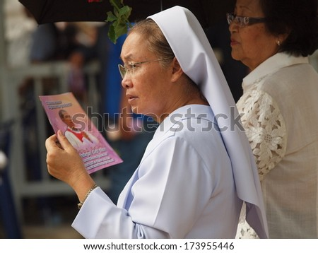 UBON RATCHATHANI, THAILAND - MAR 19, 2012 : Unidentified nun holding book of mourning for priest Luca Santi Wancha in his funeral on Mar 19, 2012 in Ubon Ratchathani, Thailand