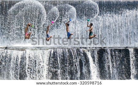 UBUD, BALI, INDONESIA-Sept 19, 2015: The boys were having fun by playing water in an artificial dam on the Tukat Unda dam, Bali, Indonesia. Bali island is a popular tourist destination in the world - stock photo