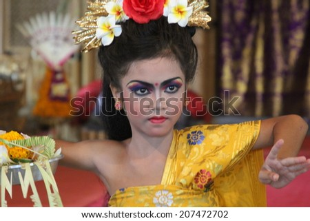 UBUD, INDONESIA-April 13: A costumed dancer performs a traditional Balinese dance with elaborate makeup and costuming before an audience on April 13, 2014.  - stock photo