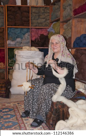 UCHISAR, TURKEY - SEPTEMBER 1, 2012: Islamic woman making yarn for a rug at Gallery Cappadocia on September 1, 2012.  Gallery Cappadocia continues to win awards in International Carpet Competitions.