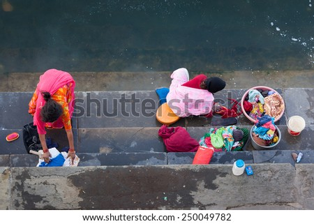 UDAIPUR, INDIA - JANUARY 16, 2015 : Aerial view of two women washing clothes on the steps of Lal Ghat next to Lake Pichola.  - stock photo