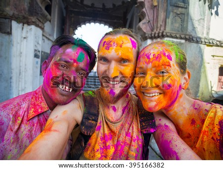 Udaipur, India - March 6, 2015: Selfie photo of Indian man and foreign couple with painted face celebrating the colorful festival of Holi on the street. - stock photo