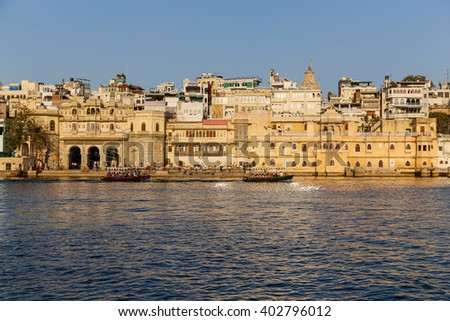 UDAIPUR, INDIA - 20TH MARCH 2016: A view of part of the Udaipur Skyline during the day. Boats, buildings and people can be seen. - stock photo