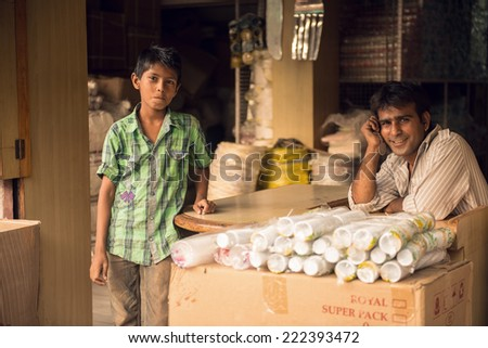 UDAIPUR, RAJASTAN - INDIA: MAY 27 2013 - Unidentified father with his son outside their store on May 27, 2013 in Udaipur, India. - stock photo