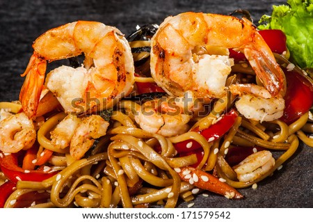 Udon noodles with vegetables and boiled prawns - stock photo
