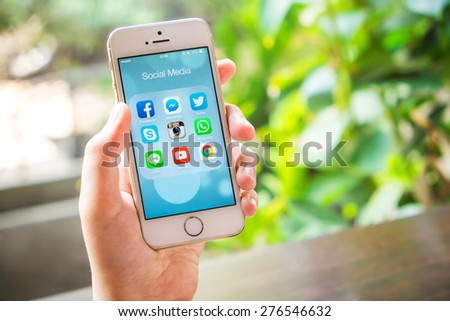 UDON THANI, THAILAND - April 19, 2015: All of popular social media icons on smartphone device screen with hand holding on Apple iPhone 5s. - stock photo