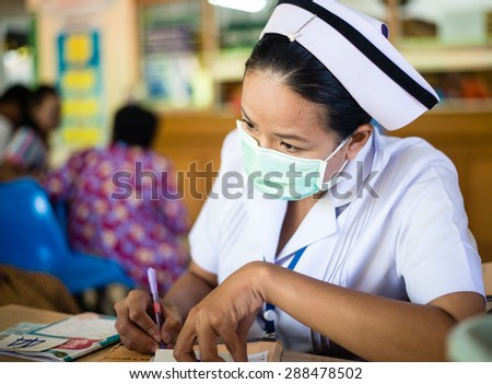 UDONTHANI THAILAND-JUNE 18 2015: Asia nurse: Woman nurse working at hospital writing medical report.