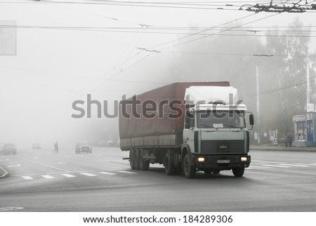 UFA, RUSSIA - OCTOBER 10, 2010: Grey MAZ 5432 semi-trailer truck at the city street during a heavy fog.