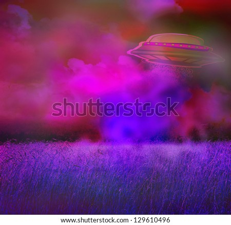 UFO over a crop field on a dark sky - stock photo