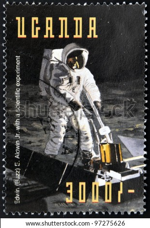 UGANDA - CIRCA 1998: Stamp printed in Uganda shows Edwin Buzz Aldrin conducts Soil Samples experiments for life forms Earth from the moon during the Apollo11 Space Mission to the Moon, circa 1998 - stock photo