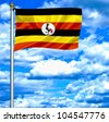 Uganda waving flag against blue sky - stock photo