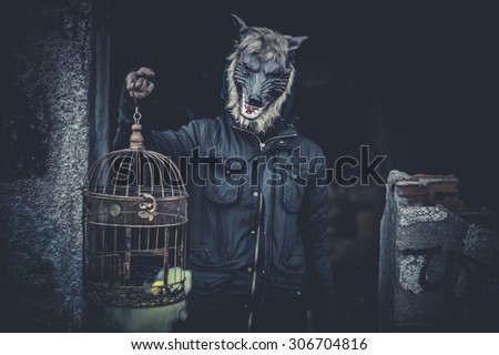 Ugly, man with mask wolf and lamp with colored smoke - stock photo