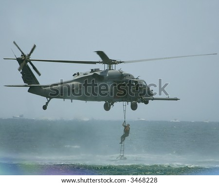 UH-60 Black Hawk. Soldier climbing up ladder on to A UH 60 Black Hawk which is a utility tactical transport helicopter . - stock photo