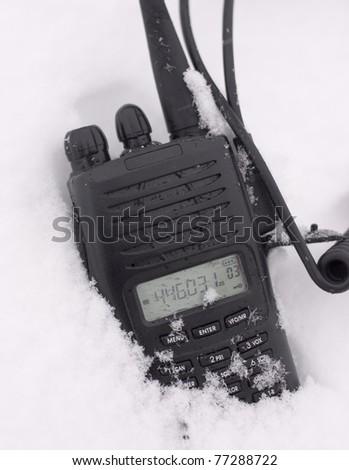 UHF 2way radio laying in the snow - stock photo
