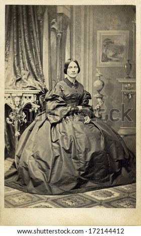UK - ENGLAND - CIRCA 1862 - A vintage Cartes de visite photo of a young woman sitting in a chair. She is dressed in hoop skirt dress with pagoda sleeves. Photo from the Civil War era. CIRCA 1862 - stock photo