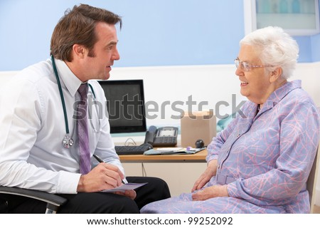 UK GP talking to senior woman patient - stock photo