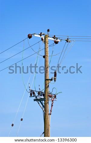 UK-style overhead powerline mast against clear blue sky - stock photo