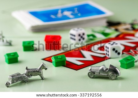 Ukraine, Kiev - October 29, 2015: Close-up view of Monopoly game pieces: car, pair of dice, houses, cards on board. Focus on the toy car - stock photo