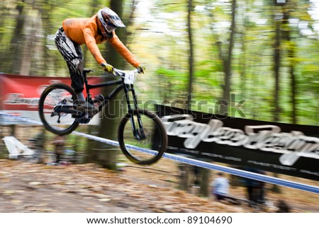 UKRAINE, KIEV - OCTOBER 16: Unknown professional biker with blurred background making his road, at the professional bicycle downhill final competition Kyiv Cup, on October 16, 2011 at Ukraine, Kiev. - stock photo