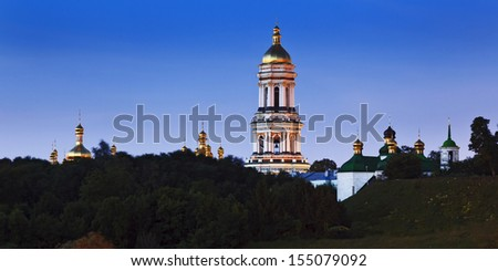Ukraine Kiev Pechersk Lavra complex of churches with tall bell tower panoramic view above trees at sunrise blue sky golden domes - stock photo