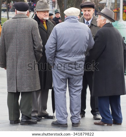 UKRAINE. LVIV - NOVEMBER 15, 2015: Active retirement, group of old male friends talking and laughing  in public park in Lviv, Ukraine