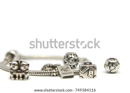 Ukraine, 11.04.2017: Pandora Charm set collection I love travel. Heart, globe, kitties, journey, passport, suitcase. Silver beads charms bracelets isolated white background. Photo Macro shot jewelry.