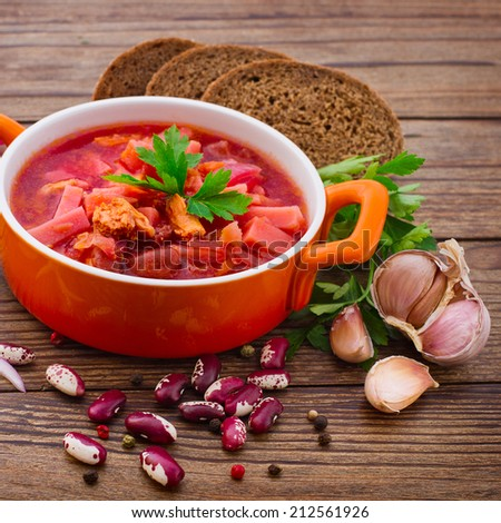 Ukrainian and Russian national Red Borscht with Bread closeup on Old Wooden Surface. Food, meat, spices for cooking meat. Free space for text.