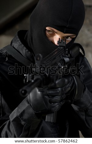 Ukrainian armed forces in black uniform and black mask. Elite swat team member armed with automatic big gun. Confident and serious man with American rifle. Portrait of unknown soldier
