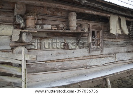 ukrainian authentic wooden hut wall with vintage home-made household tools in village Kolochava - stock photo