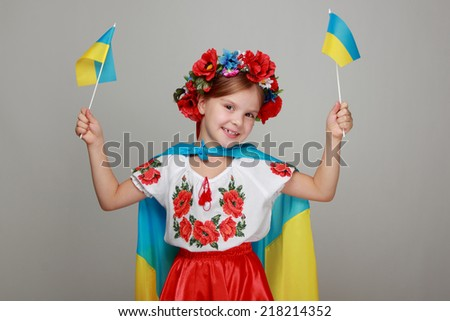 Ukrainian Beautiful little girl with a sweet smile, holding a big flag of Ukraine and is a fan of football competition - stock photo