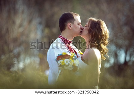 Ukrainian brides in traditional costumes embroidered shirts outdoors kiss - stock photo